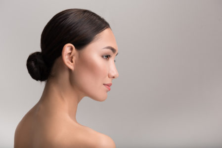 Image of the profile of a female model with her hair pulled into a tight low-bun.